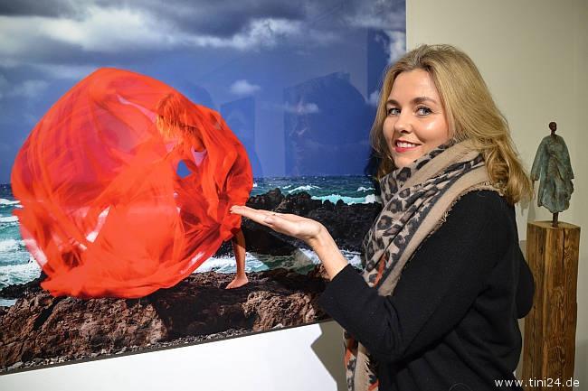 Model Jule, die extra zur Matinee der Ausstellung erschienen ist, zeigt auf ein ausgestelltes Foto, auf der sie zu sehen ist.