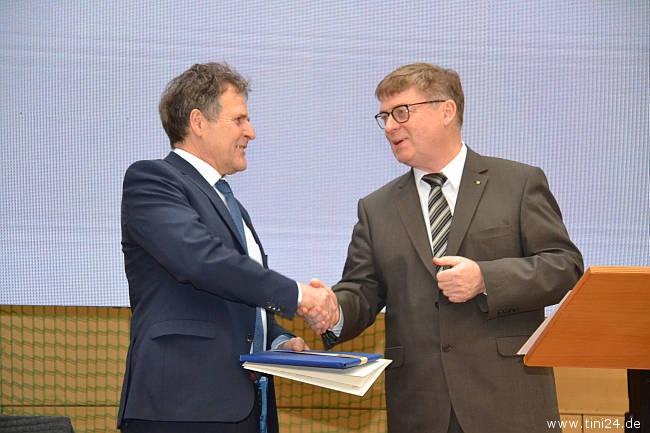 Ostholsteins Schulrat Manfred Meyer (rechts) überreicht die von Bildungsministerin Karin Prien unterschriebene Urkunde und ein Buchpräsent an den ausscheidenden Schulleiter. (Foto: René Kleinschmidt)